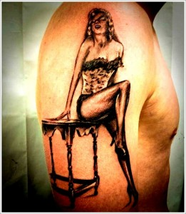 Pinup girl tattoo on the biceps