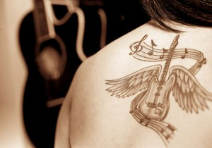 Back guitar and musical notes tattoo design