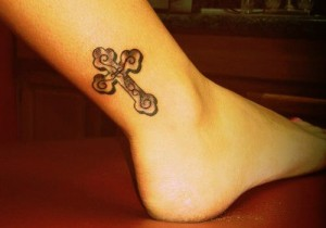 Beautiful cross tattoo above the ankles