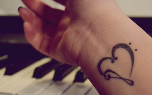 Black heart and musical note tattoo design on wrist