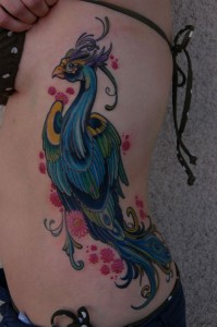 Bright and colourful bird tattoo on ribs