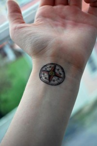 Red and black compass tattoo design on wrists