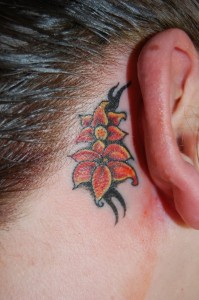 Small lily flower tattoos behind the ear