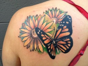 Black butterfly and flower tattoo on shoulder