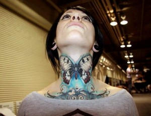 Colourful butterfly tattoo on neck