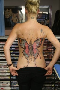 Pink and black butterfly tattoo on back