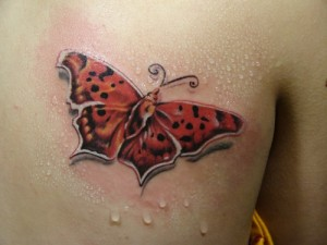 Red butterfly tattoo on back