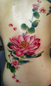 Lotus flower tattoo with green vines
