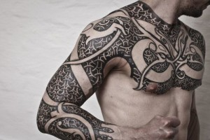 Tribal Chest To Arm Tattoo