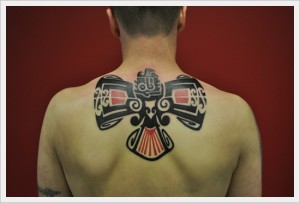 Red And Black Tribal Upper Back Tattoo