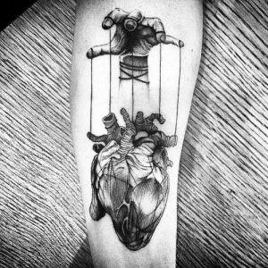 Black And Grey Ink Heart Puppet Forearm Tattoo