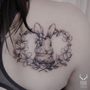 Adorable Rabbit With Floral Wreath Back Tattoo