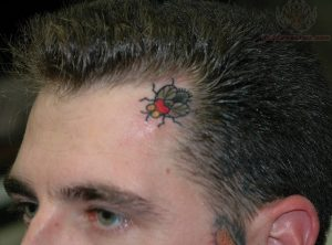 Red Fly Forehead Tattoo