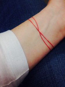Red Strings Wrist Band Tattoo