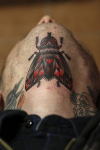 Red and Black Fly Under Chin Tattoo
