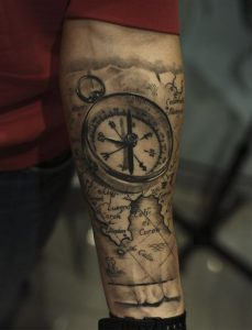 Realistic Metal Lid Compass Over Old World Map Forearm Tattoo