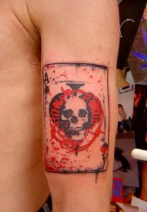 Red Paint-Splashed Skull Ace of Spades Biceps Tattoo