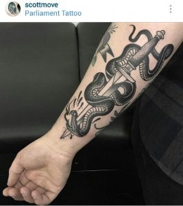 Black Snake Stabbed by a Dagger Forearm Tattoo