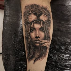 Straight-Faced Woman with Lion Headdress Calf Tattoo