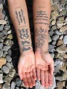 Sanskrit Passage with Fishes and Flower Forearm Tattoo