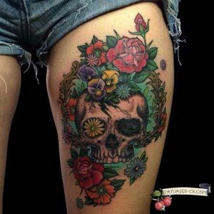 Skull Over a Bunch of Flowers Thigh Tattoo