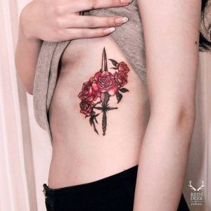 A Dagger and Five Roses Side Tattoo