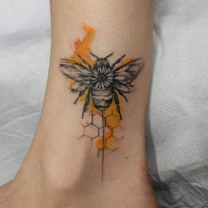 Color Splattered Bee And Honeycomb Leg Tattoo